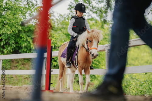 Fotografie, Obraz  Caucasian girl with helmet and protective vest on riding cute white and brown pony horse