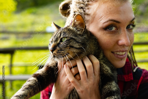 Loving young woman cuddling her cat to her cheek - 282603196