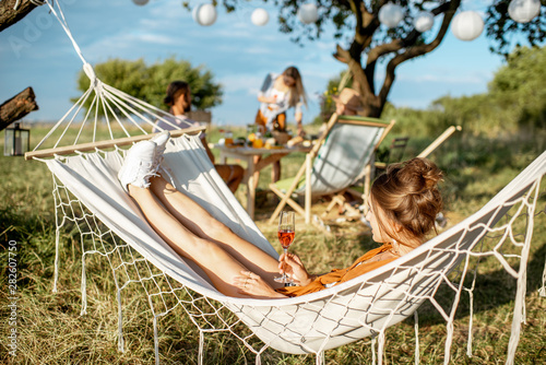 Young woman relaxing with wine glass on the hammock, during a lunch with friends in the garden on a summer afternoon