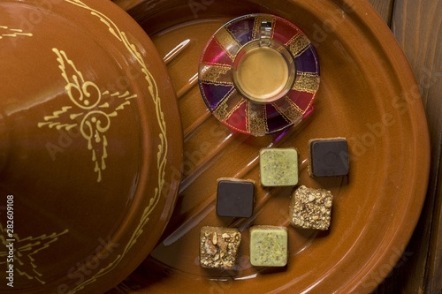 Overhead shot of different types of square-shaped sweets with tea on a wooden tray #282609108