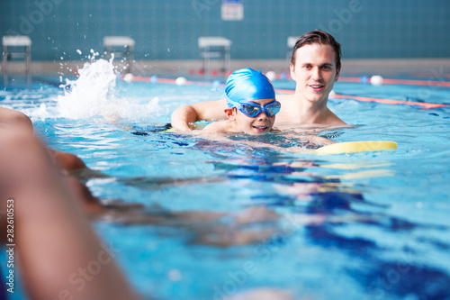 Fototapeta Male Coach In Water Giving Group Of Children Swimming Lesson In Indoor Pool