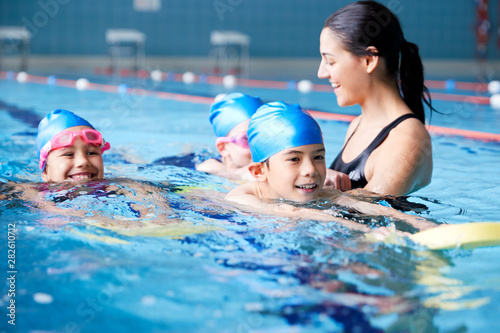 Fotografia Female Coach In Water Giving Group Of Children Swimming Lesson In Indoor Pool