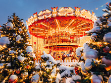 Beautiful Brightly Glowing Carousel On The Red Square Decorated And Arranged For Christmas And New Year. Christmas Fairy Illuminated Turnabout . Luminous Roundabout Rotates. Wonderful Magic Xmas