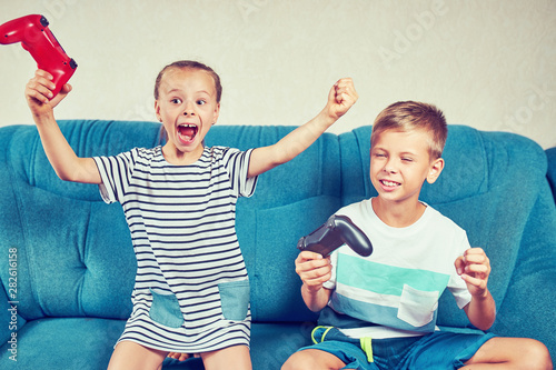 Children emotionally play a video game while sitting on the couch Wallpaper Mural