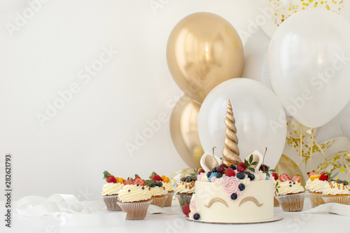 Fotomural  Close up of little girl's birthday party table with unicorn cake