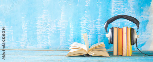 Cuadros en Lienzo  audio book concept with open book, row of books an headphones, panorama format o