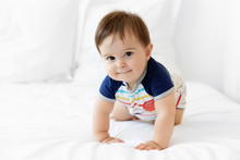 Cute Baby Crawling On White Bed Looking At Camera