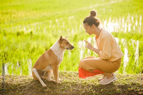 Vászonkép asian thai woman farmer talking with her dog to sitting