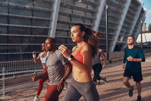 Fotografía  Group of young people in sports clothing jogging together outdoors