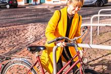 Young Girl Tethering Bicycle O...