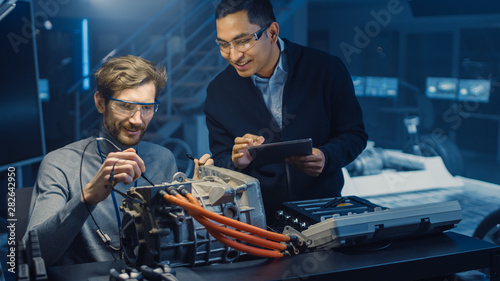 Two Professional Automotive Engineers with a Tablet Computer and Inspection Tools are Having a Conversation While Testing an Electric Engine in a High Tech Laboratory with a Concept Car Chassis Canvas Print