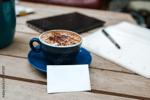 Wall Murals Cafe Closeup shot of cappuccino in a blue ceramic cup, a black tablet and notebook on the table