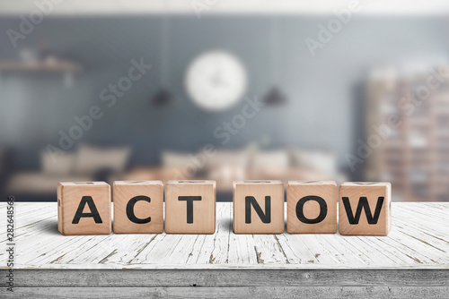 Act now message sign on a wooden desk Wallpaper Mural