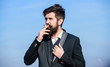 Guy with cigarette enjoy nicotine influence. Pleasure of smoking. Relaxing but harmful habit. Man with beard and mustache hold cigarette. Bearded hipster smoking cigarette blue sky background