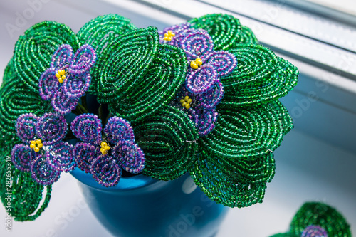 Bouquet of violets woven from beads in a blue ceramic vase
