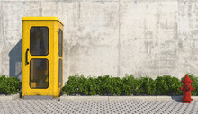 Single Old Yellow Phone Booth In Retro Style On The Footpath In The Urban Exterior Opposite The Facade Of The Concrete Wall And Red Fire Hydrant. 3D Render.