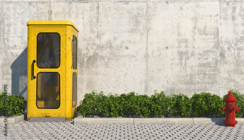 Fototapeta  Single old yellow phone booth in retro style on the footpath in the urban exterior opposite the facade of the concrete wall and red fire hydrant
