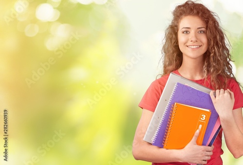 Foto auf AluDibond Akt Portrait of a cute young student girl holding colorful notebooks, isolated on background