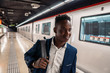 African American businessman wearing blue suit and backpack in metro subway. Business concept