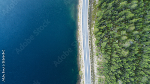 Foto auf AluDibond Pistazie Aerial top view of a country road through a forest and a lake in summer in rural Finland