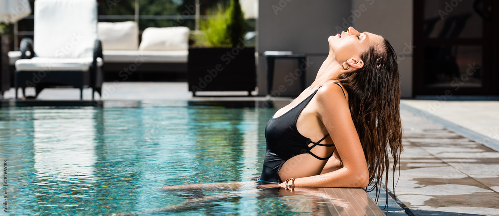 Fototapeta panoramic shot of attractive sexy woman in swimming suit posing in pool on resort
