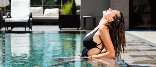Foto panoramic shot of attractive sexy woman in swimming suit posing in pool on resor