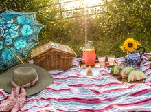 Beautiful Country Picnic In Soft Light Meadow With Basket Sunflowers In Pitcher Watermelon Pink Lemonade Pimiento Cheese On Colorful Striped Cloth, Sun Dappled