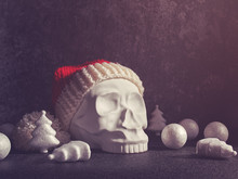 A Red Santa Claus Hat Is Put On A Decorative Sculpture In The Form Of A Human Skull. Nearby Are Balls And Figures In The Form Of A Christmas Tree. Gray Cement Background With Cracks And Scuffs.