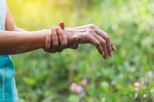 closeup hand of person holding arm his fill pain on for healthy concept on nature background Fototapeta