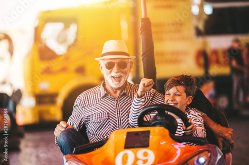 Slika na platnu Grandfather and grandson having fun and spending good quality time together in amusement park