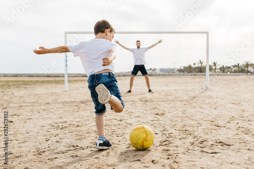 Man and boy playing soccer on the beach