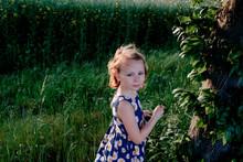 Portrait Of Girl Standing In Meadow