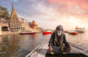 Indian sadhu baba on a wooden boat overlooking ancient Varanasi city architecture with Ganges river ghat at sunset