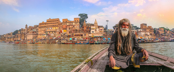 Indian sadhu on a wooden boat overlooking panoramic view of ancient Varanasi city architecture with Ganges river ghat