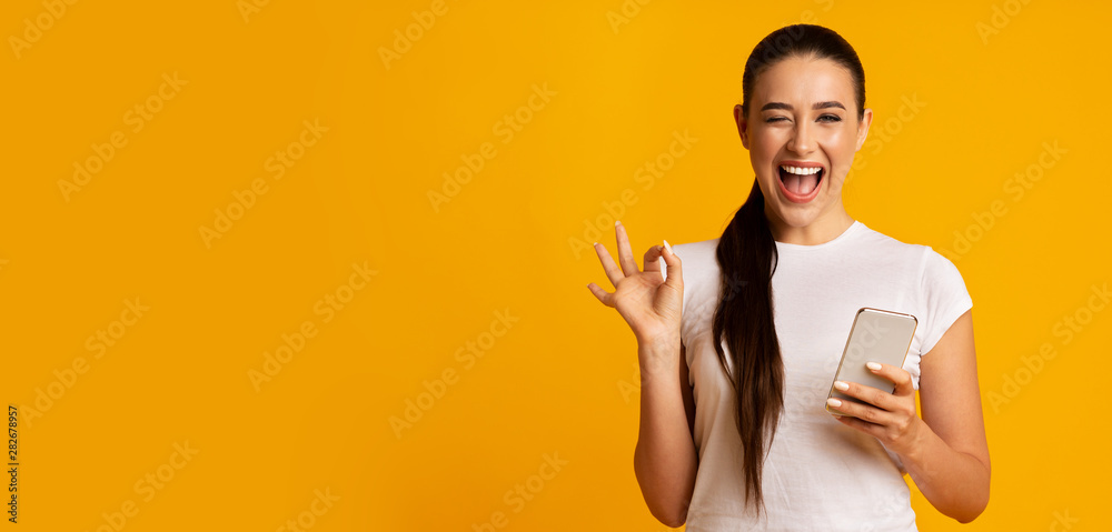 Fototapeta Woman Holding Phone And Gesturing OK Sign Over Yellow Background