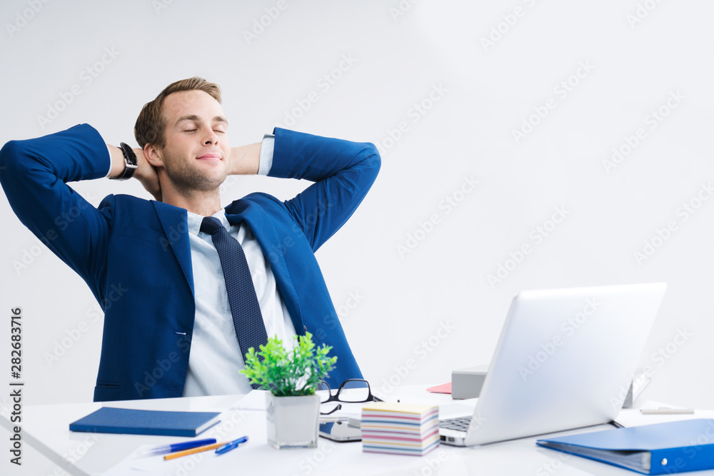 Fototapeta Relaxing or dreaming businessman with hands behind head, in blue suit working with laptop computer at office