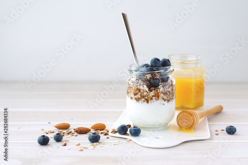 Foto Healthy breakfast in glass jar with yogurt, muesli and blueberries