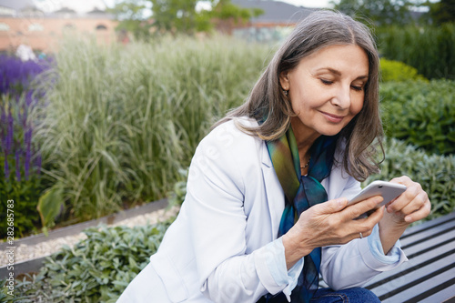 Fotografiet  Summertime image of gray haired beautiful retired female sitting on bench with portable electronic gadget, chatting online via messenger