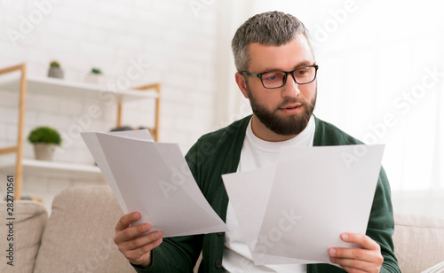Fotografija Handsome man holding papers with both hands, reading it