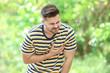 Leinwandbild Motiv Young man suffering from heart attack outdoors