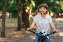 Young Woman Riding Bicycle Out...