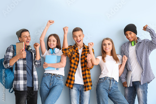 Fotomural  Portrait of happy young students on color background