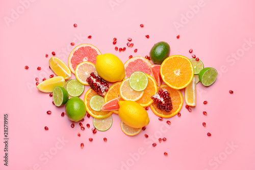 Leinwand Poster Different sliced citrus fruits on color background