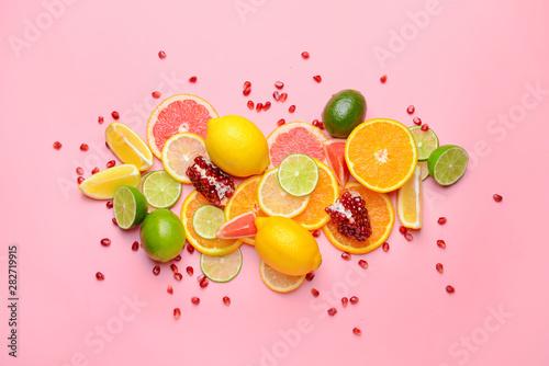 Obraz na plátně  Different sliced citrus fruits on color background