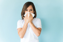 Sick Woman Suffering From Flu Against Plain Background