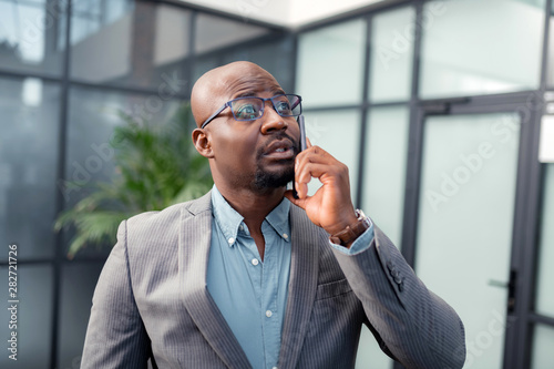 Dark-skinned bearded man calling business partner from office