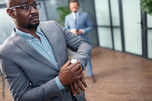 Dark-skinned businessman feeling concerned before important meeting