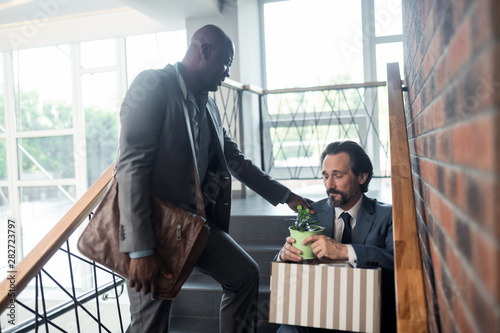 Dark-skinned friend speaking with colleague after getting redundant Canvas Print