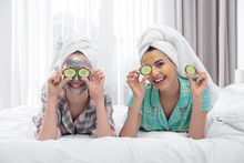 Young Friends With Facial Masks Having Fun In Bedroom At Pamper Party