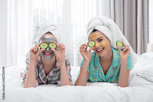 Carta da parati Young friends with facial masks having fun in bedroom at pamper party
